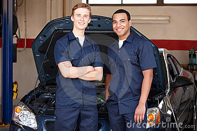 Mechanics standing in front of car