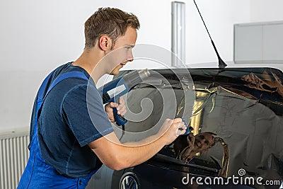 Mechanik zabarwia samochodowego okno z zabarwiającym filmem lub folią