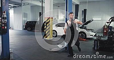 Mechanischer Mann in einem gleichmäßigen Tanz lustig in einem großen Service Auto-Center hat er eine große Stimmung bei der Arbei stock footage