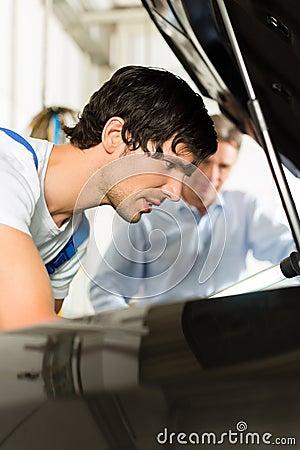 Mecánico del hombre y de coche que mira debajo de un capo motor
