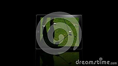Medias pantallas del dispositivo que muestran golf almacen de metraje de vídeo