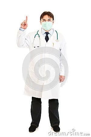 Medical doctor in mask pointing  finger up