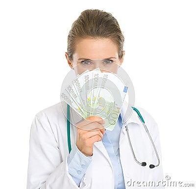 Medical doctor woman hiding behind fan of euros