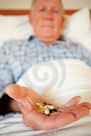 Medical pills in the hand of an elderly man