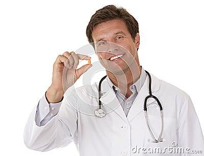 Medico che tiene una pillola
