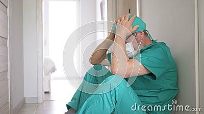 Medico stancato appoggiato al muro in ospedale archivi video