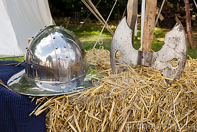 Medieval helmet and axe on hay