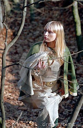 Medieval woman walking in forest