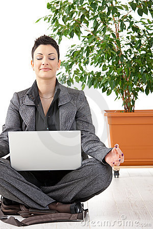 Meditating businesswoman with laptop