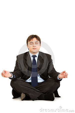 Meditating modern businessman sitting on floor