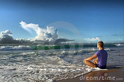 Meditating young man faces big wave