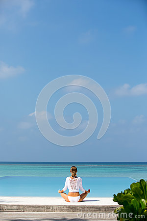 Free Meditation. Photo Of A Woman Who Is Sitting In The Lotus Position On The Ocean Coast. Maldives Royalty Free Stock Images - 88725129