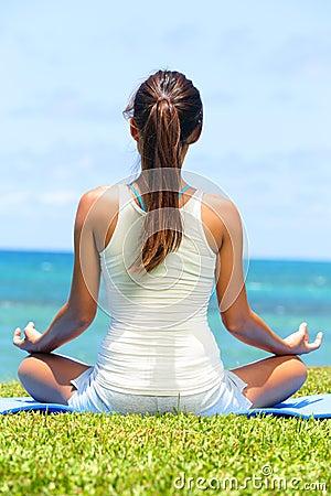 Meditation yoga woman on beach meditating by ocean