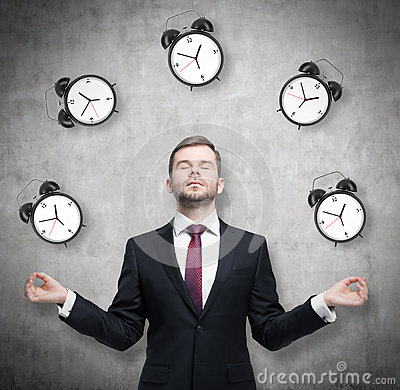 Free Meditative Businessman Is Pondering About Time Management. The Person In Formal Suit Is Surrounded By Alarm Clocks. There Is A Con Royalty Free Stock Photography - 62006817
