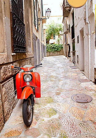 Mediterranean street with old retro red scooter