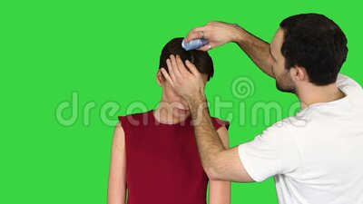 Beauty, hairstyle and people concept - young woman with hairdresser with hair spray on a green screen, chroma key. Medium shot. Beauty, hairstyle and people stock video footage