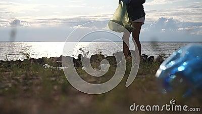 Meeresküste mit Plastikflaschen verseucht Eine junge Frau reinigt die Umwelt stock video