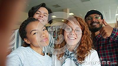 Meerraciale groep jongeren die zichzelf in de collegebibliotheek laten zien glimlachen stock videobeelden