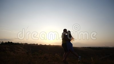 A meeting of a young charming couple in rural landscape at sunset. Silhouette of bearded young man and his girlfriend. A couple in love in the sunset light stock video