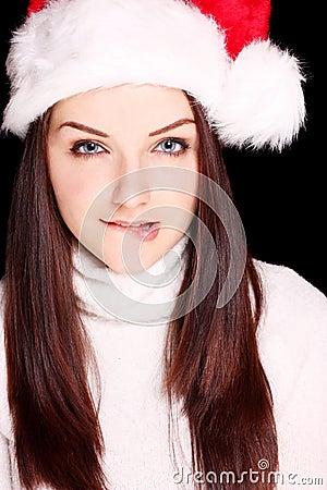 Meisje dat haar lip bijt die de hoed van de Kerstman draagt