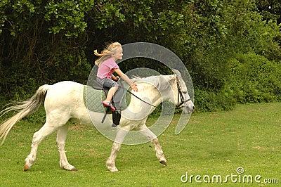 Meisje dat haar poney berijdt