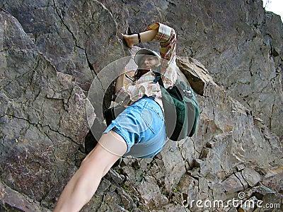 Meisje dat rotsen beklimt, die aan de piek van de berg streven