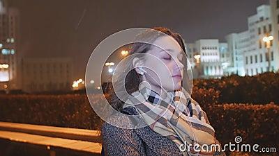 Meisje die aan muziek op hoofdtelefoons luisteren en de avondlichten doornemen van de stad onder de huizen koude snowing stock video