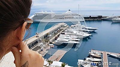 Meisje die cruisevoering bekijken van hotelterras, die op inscheping op schip wachten stock footage