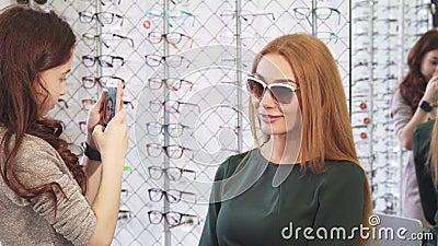 Meisje die foto's van haar mooi mamma nemen die voor zonnebril winkelen stock video