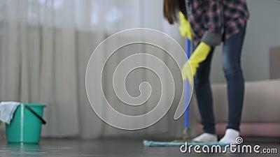 Meisje die zorgvuldig vloer van hotelruimte wassen vóór aankomst van gasten, het schoonmaken stock videobeelden