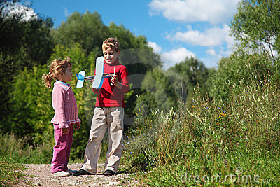 Meisje en jongen met stuk speelgoed vliegtuig in handen