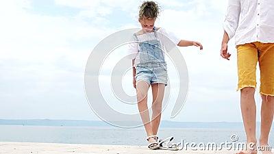 Meisje en jongen op een zeeligplaats Meisje neemt haar sandalen af en gaat barefoot, zomervakantie, gelukkige kinderen stock footage