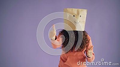 Meisje met document zak bij het hoofd dansen die duim-op het tonen als teken tonen stock footage