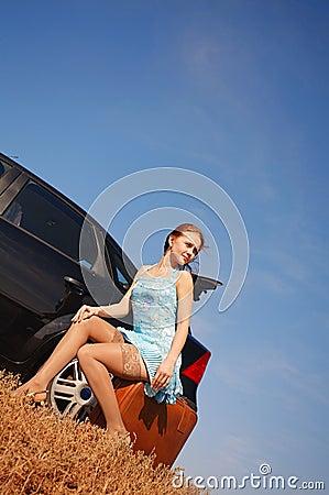 Meisje met koffer dichtbij de auto