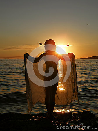 Meisje in zonsondergang met sjaal en vogels