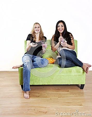 Meisjes die op het lachen van TV letten