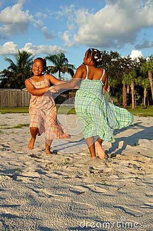 Meisjes die op zand bij strand dansen