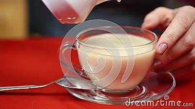 Meisjes gietende melk in zwarte thee Echte gastronomisch Voorbereiding van smakelijke drank stock footage