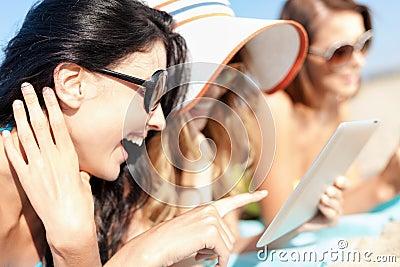 Meisjes met tabletpc op het strand