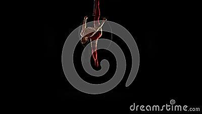 Meisjesacrobaat in rode maillotbovenkant - onderaan been hang op luchthoepel op zwarte achtergrond stock footage