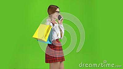 Meisjesstappen rond met pakketten en besprekingen Het groene scherm Zachte nadruk stock footage