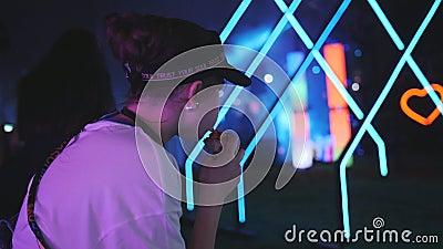 Meisjestiener eet 's avonds een hotdog op de achtergrond van disco in een nachtclub in de openlucht Neon party stock footage