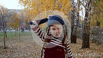 Meisjestiener in gestreepte kleren en blauw kapje met geel maple blad in de buurt van kop als kraai Portret blij meisje met stock footage