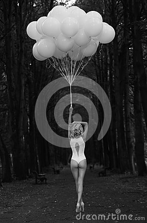 Melancholy. Lonely Woman with Balloons in Dark and Gloomy Forest