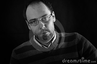 Melancholy look of a man with beard glasses