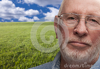 Melancholy Senior Man with Grass Field Behind