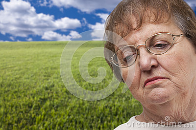 Melancholy Senior Woman with Grass Field Behind