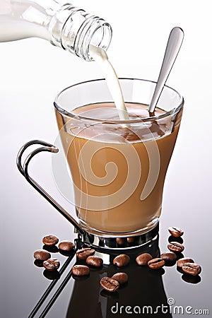 Melk die in koffie wordt gegoten