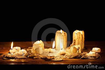 Melting candle in wooden shelf