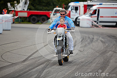 Member from stuntmen team rides motorcycle with child Editorial Stock Image